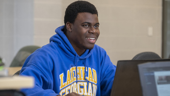 Male student wearing a Lakehead-Georgian blue sweatshirt while using a laptop computer and smiling