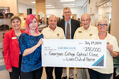 Group holds up large cheque for $250,000
