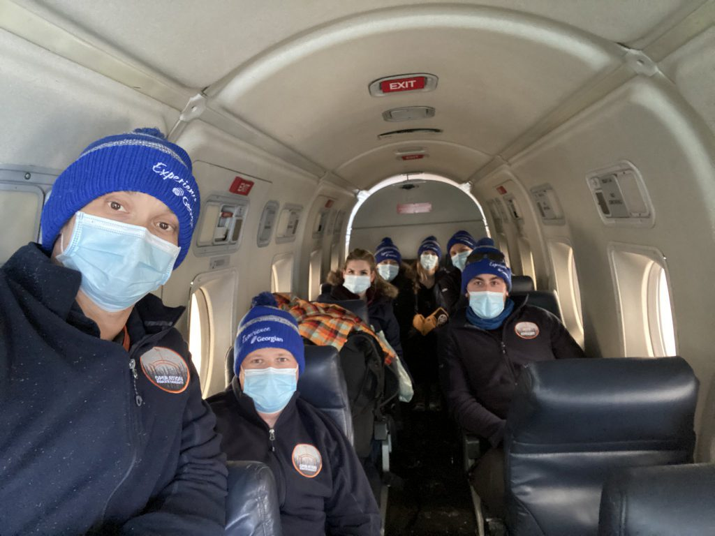 """A group of people inside a small airplane, all wearing face masks and hats that read """"Experience Georgian."""""""