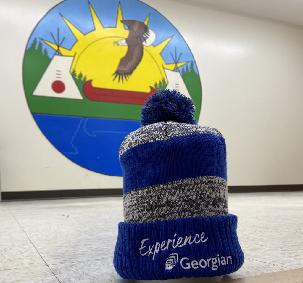 """A toque with the words """"Experience Georgian"""" on it sits on the floor in front of a mural."""