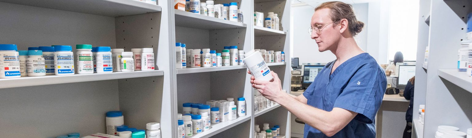 Pharmacy Technician in blue scrubs and glasses reading a medicine bottle in front of shelves full of prescription medication