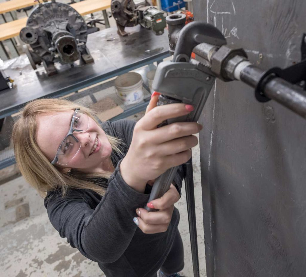 female power engineering technology student at Georgian's Owen Sound campus using a wrench on a piece of machinery