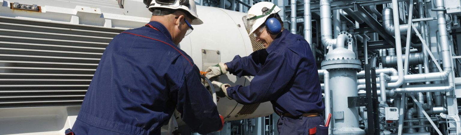 Two power engineering professionals wearing work jumpsuits and hard hats working on a piece of equipment