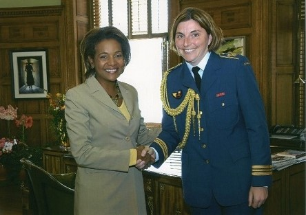 Rebecca and former Governor General Michaëlle Jean shaking hands (Black woman in light grey dress suit and yellow top, white woman in Canadian Forces blue uniform)