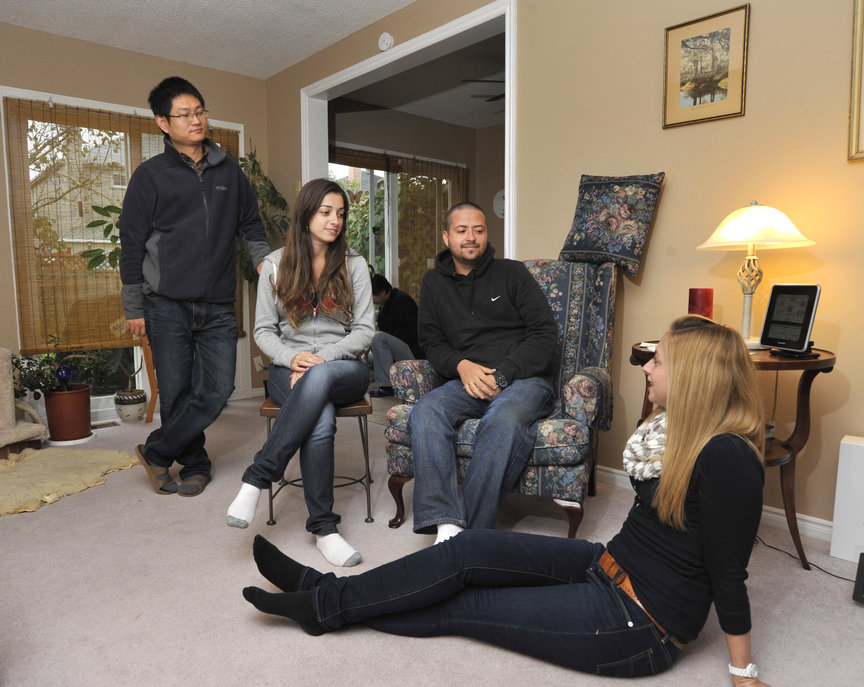 Four students hanging in a living room