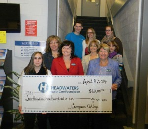 Students stand on staircase holding large cheque
