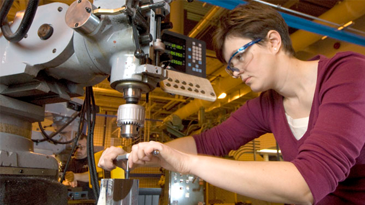 female student wearing safety goggles working with precision equipment at Georgian's Barrie Campus