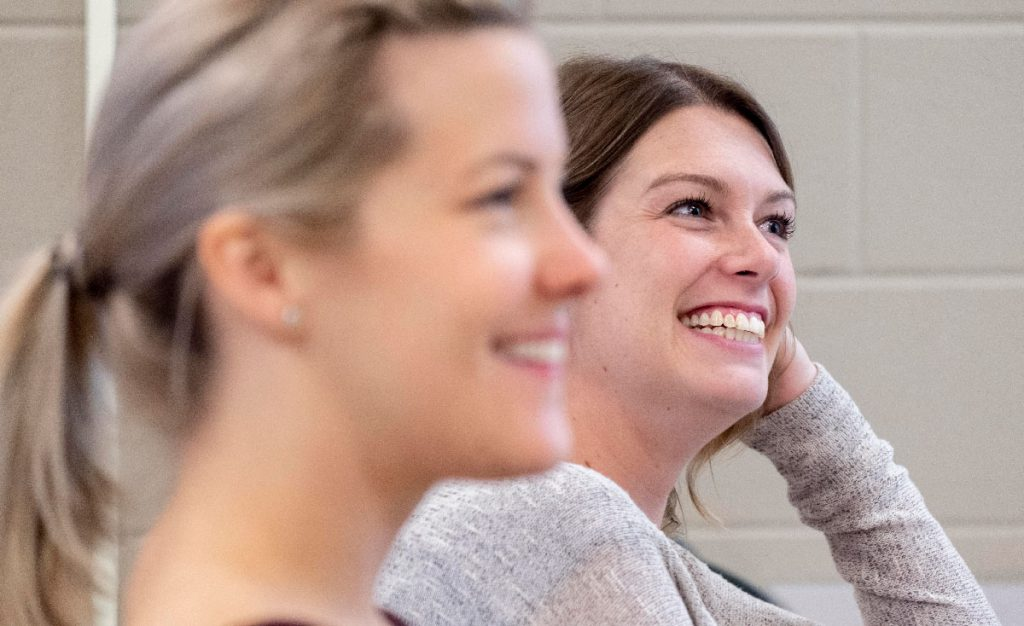 two female social service worker students smiling while in class