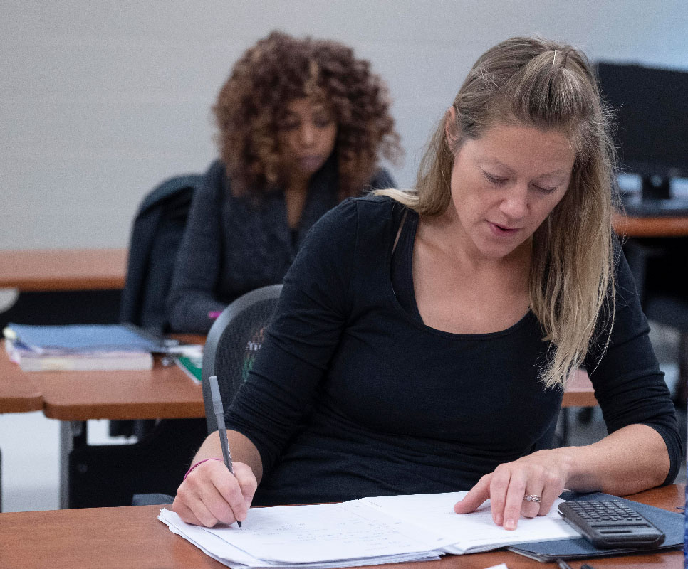female student with blonde hair and a black shirt writing in a notebook and using a calculator
