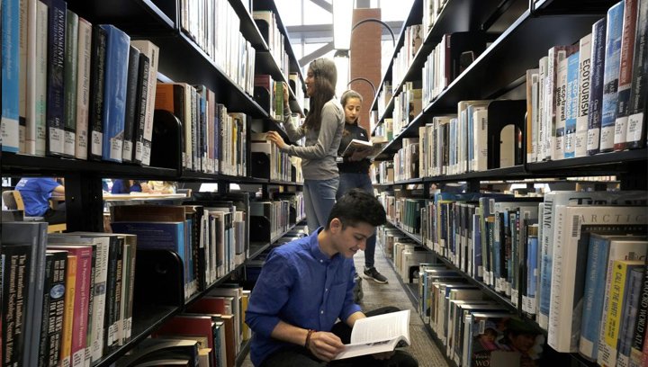 Three students standing between the book shelves at the library reading