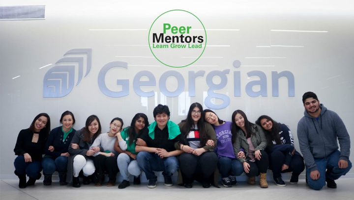 a group of peer mentors kneeling in front of a Georgian College logo