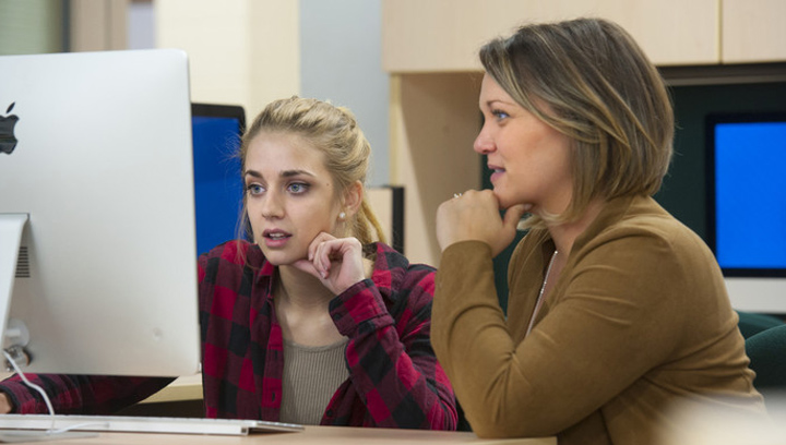 student advisor assisting a student on a Mac computer