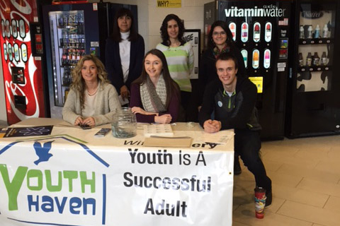 A group of students stand behind a table with a Youth Haven banner draped in front